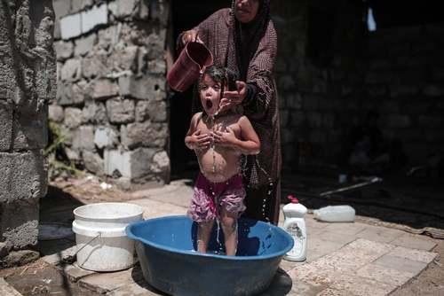 شستشوی یک بچه در حیاط خانه در نوار غزه/ خبگراری آناتولی