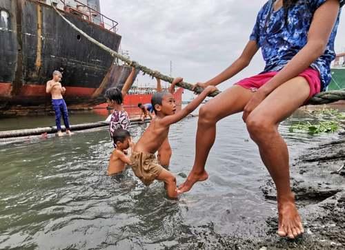 کودکان فیلیپینی در حال بازی در کنار کشتیها در بندری در مانیل/ EPA