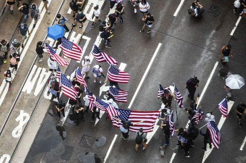 پرچم آمریکا و پوستر دونالد ترامپ در دست معترضان هنگ کنگی. معترضان از ترامپ کمک خواستند تا هنگ کنگ را آزاد کند./ بلومبرگ