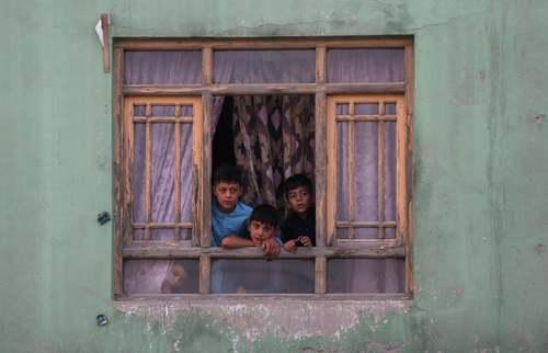 کودکان افغان در حال تماشای صحنه یک انفجار انتحاری از پنجره خانه در شهر کابل/رویترز