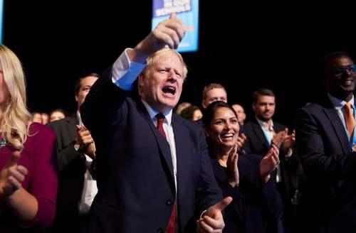 نخست وزیر بریتانیا در حال تشویق یک سخنران در کنفرانس سالانه حزب محافظهکار در منچستر/ گاردین