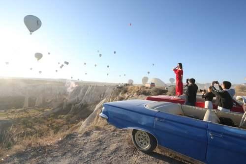 گردشگران در حال عکس و فیلم گرفتن از بالنها در شهر گردشگری