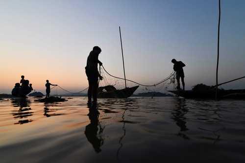 آماده کردن تور از سوی ماهیگیران هندی در ساحل