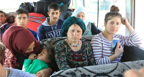 آوارگان جنگی کرد سوریه که پس از حمله ارتش ترکیه به شمال سوریه آواره شدهاند داخل اتوبوسی به سمت اردوگاهی در شهر
