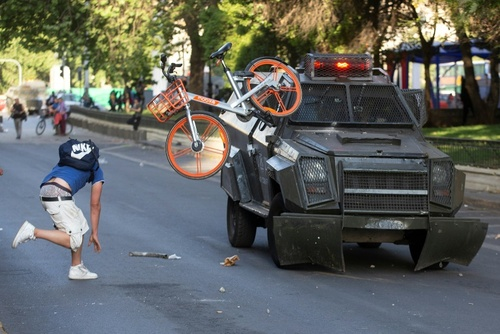پرتاب دوچرخه یک معترض به سمت خودروی نیروهای امنیتی - شهر سانتیاگو پایتخت شیلی  جمعه 26 مهر 98  عکس: خبرگزاری فرانسه - كلاوديو رييس
