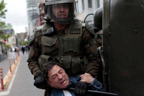 یک معترض و نیروهای امنیتی - سانتایگو پایتخت شیلی عکس: خبرگزاری رویترز