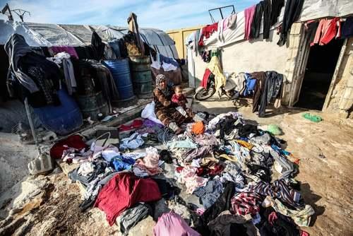 زن آواره سوری در اردوگاهی در استان ادلب در شمال غرب سوریه در حال خشک کردن لباسهای خانواده پس از یک باران شدید/ خبرگزاری آناتولی
