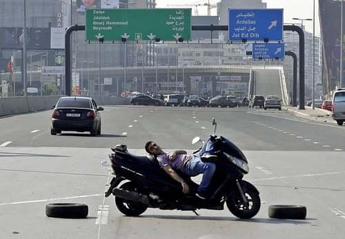معترض لبنانی با موتورسیکلت خود بزرگراهی در شهر بیروت را بسته است./ خبرگزاری فرانسه