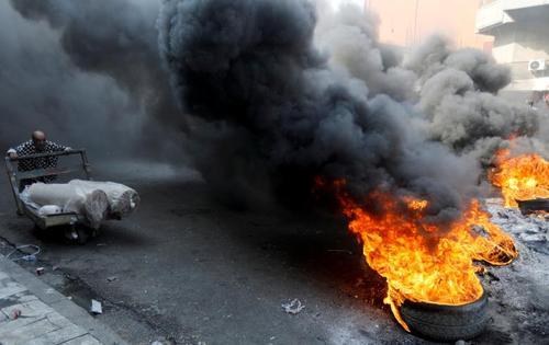 آتش زدن لاستیک خودرو از سوی معترضان عراقی در شهر بغداد/ رویترز