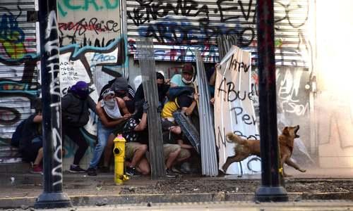 یک سگ در صف معترضان شیلیایی و علیه پلیس ضد شورش (شهر سانتیاگو)/ خبرگزاری فرانسه و رویترز
