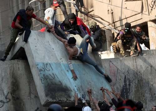 کمک به یک معترض در جریان اعتراضات دیروز (سهشنبه) در شهر بغداد/ رویترز