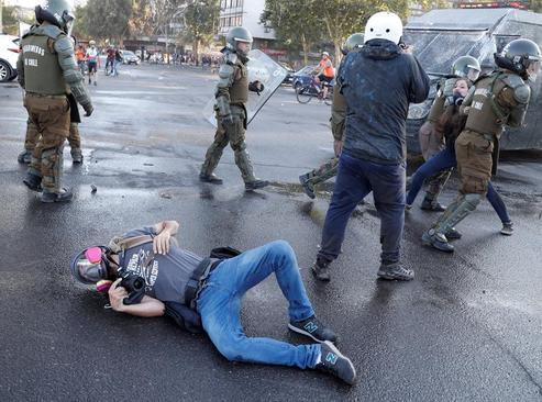 افتادن یک عکاس خبری به روی زمین در جریان ناآرامیهای شهر