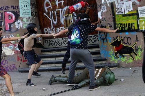 به زمین افتادن یک نیروی پلیس ضد شورش شیلیایی در جریان مقابله با اعتراضات ضددولتی در شهر سانتیاگو شیلی/ رویترز