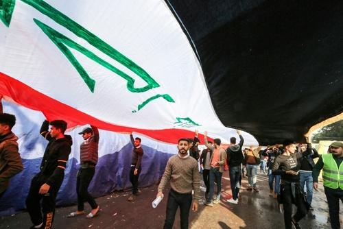 تظاهرات معترضان با پرچم بزرگ عراق در میدان تحریر بغداد/ خبرگزاری فرانسه