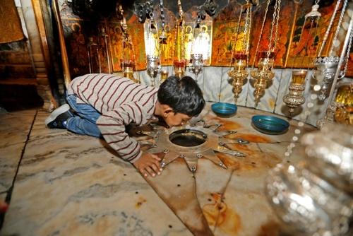 بوسه یک زائر مسیحی بر محل تولد عیسی مسیح در کلیسای مهد در