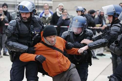دستگیری یک کارمند اعتصاب کننده راهآهن فرانسه در هجدهمین روز از اعتصابات سراسری در پاریس. معترضان اعتصاب کننده بخش حملونقل عمومی فرانسه، به طرح دولت