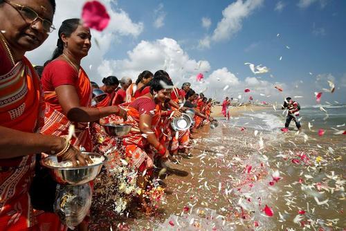 پانزدهمین سالگرد سونامی مهیب هند. زنان در حال ریختن گل به خلیج بنگال در