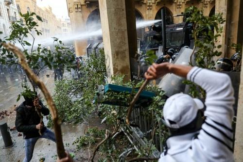 خبرگزاری فرانسه - انور عمرو /حمله معترضین به نیروهای امنیتی با استفاده از درخت های کنده شده از خیابان در بیروت  - 18 ژانویه 2020 (28 دی 98)