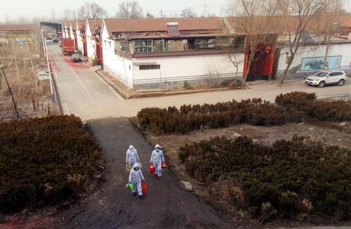 داوطلبان با البسه مخصوص در حال حمل غذا و مایحتاج روزانه به خانههای قرنطینه شده روستایی در چین/ رویترز