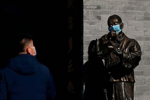 ماسک روی صورت مجسمه برنزی مقابل فروشگاهی در شهر پکن چین/ گتی ایمجز