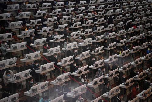 معامله گرانی که ماسک به صورت دارند در حال کار در مرکز تجارت و حراج گل در شهر