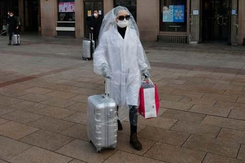 ایستگاه قطار شهر پکن و مسافرانی که خود را برای جلوگیری از ابتلا به ویروس کرونا باندپیچ کردهاند./ EPA
