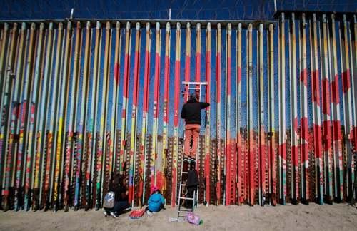 فعالان حقوق مهاجران در حال رنگآمیزی شکل قلب  روی دیوار مرزی بین ایالات متحده آمریکا و مکزیک/ EPA