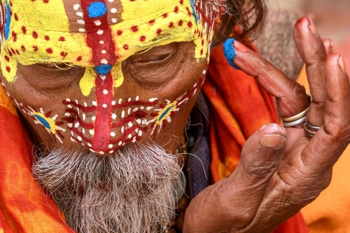 مرد مقدس هندو در حال رنگ آمیزی صورت در معبدی در کاتماندو نپال در جشنواره آیینی