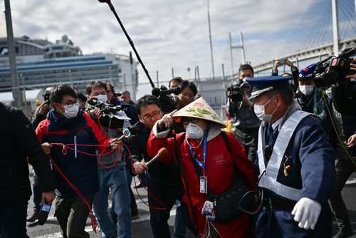 خبرنگاران ژاپنی در حال مصاحبه با مسافران پیاده شده از کشتی تفریحی قرنطینه شده