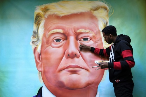نقاش هندی در حال کشیدن تصویر رییس جمهوری آمریکا روی دیوار در شهر