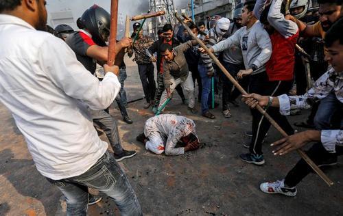 عکسی از درگیریهای فرقهای هفته گذشته در شهر دهلی هندوستان بین مسلمانان و هندوها بر سر قانون جدید شهروندی هند. در این عکس هندوهای حامی قانون در حال کتک زدن یک مسلمان معترض به قانون جدید هستند./ رویترز