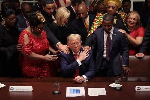حامیان آفریقایی- آمریکایی رییس جمهوری آمریکا در پایان یک نشست خبری در کاخ سفید برای ترامپ دعا میکنند./ گتی ایمجز