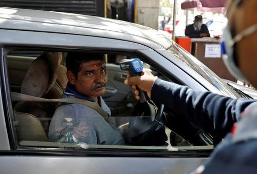 کنترل دمای بدن مراجعان به پارکینگ یک نهاد دولتی هند در شهر دهلی/ رویترز