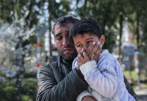مرد پناهجو در مرز ترکیه و یونان در حال جلوگیری از ورود گاز اشک آور شلیک شده از سوی گارد مرزی یونان به دستگاه تنفسی فرزندش/ خبرگزاری آناتولی