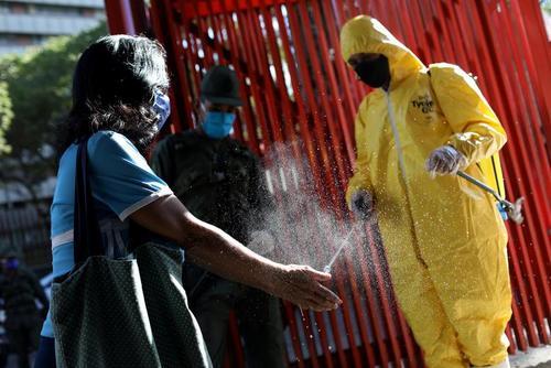 ضدعفونی دستهای مراجعه کنندگان در ورودی یک بازار در شهر کاراکاس ونزوئلا/ رویترز