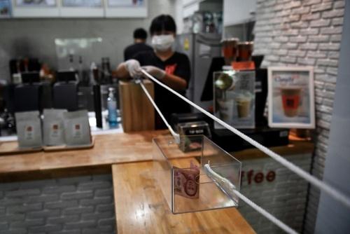 ابتکار یک کافه در شهر بانکوک تایلند برای ردو بدل کردن اسکناس کاغذی با مشتریان با رعایت فاصله 2 متری/ خبرگزاری فرانسه