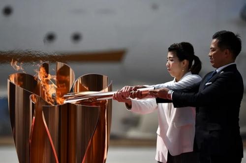 2 قهرمان المپیکی سابق ژاپن در مراسم سوت و کور روشن کردن مشعل المپیک بازیهای تابستانی 2020 توکیو در استادیومی در این شهر ژاپن/ خبرگزاری فرانسه