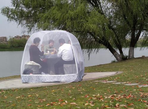 خوردن غذا در چادری محافظ از ویروس کرونا در پارکی در شهر