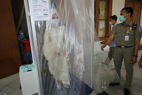 تعبیه یک ورودی گندزُدا در مقابل تالار عروسی در استان جاوه اندونزی و عروسی که هنگام ورود به مراسم در