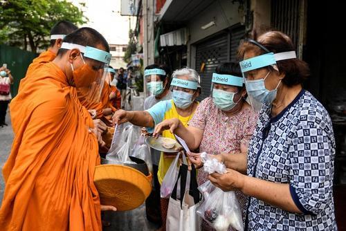 راهبان بودایی در بانکوک تایلند با رعایت تمام موارد ایمنی کرونایی در حال جمعآوری نذورات مردمی/ رویترز