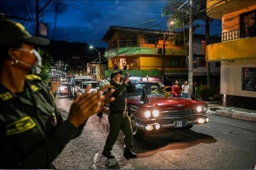 پلیس کلمبیا در حال خواندن اطلاعیه هشدار شیوع ویروس کرونا در خیابانی در شهر