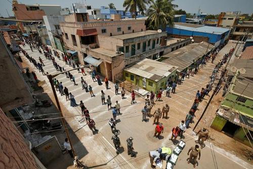 صف توزیع غذای رایگان با رعایت فاصله ایمنی از سوی پلیس در محلههای فقیر شهرهای