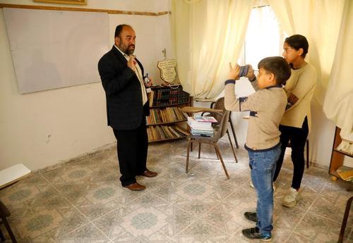 معلم فلسطینی در خانه خود در  کرانه غربی به کمک فرزندانش در حال فیلم گرفتن از جلسه تدریس خود است تا آن را به دانشآموزان خود ارسال کند./ رویترز