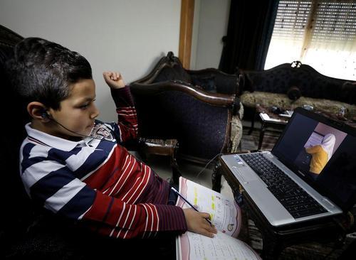 دانشآموز سوریهای در کلاس درس مجازی در منزل خود در دمشق/ رویترز