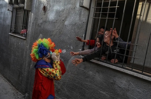 دلقک فلسطینی در حال سرگرم کردن کودکان در قرنطینه خانگی در باریکه غزه/ EPA