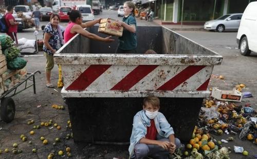 خانواده پاراگوئهای در حال جمع کردن میوههای دورریخته شده از سطل زباله در جریان 4 هفته قرنطینه سراسری  در این کشور/ آسوشیتدپرس