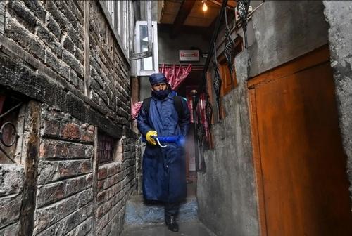 کارگر شهرداری در حال ضدعفونی یک منطقه قرمز از نظر وجود بیماران کرونایی در شهر