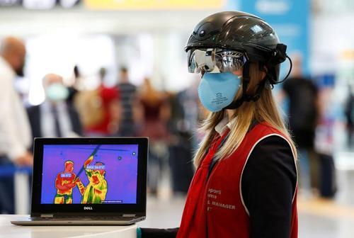 مامور فرودگاه بینالمللی شهر روم ایتالیا با کلاه هوشمند مجهز به حسگر دمای بدن مسافران و دوربین حسگر دما در حال کنترل مسافران ورودی و خروجی/ رویترز