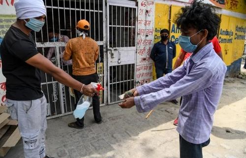 ضدعفونی کردن دستها و پول کاغذی مشتری در مقابل یک مغازه فروش مشروبات الکلی در شهر قاضیآباد هندوستان/ خبرگزاری فرانسه