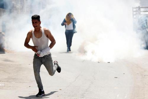 فرار جوان فلسطینی از گاز اشکآور نیروهای اسراییلی در حومه شهر